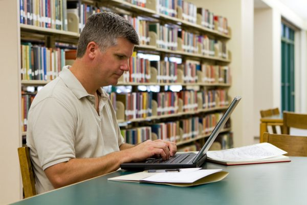 Middle aged man working on laptop in library